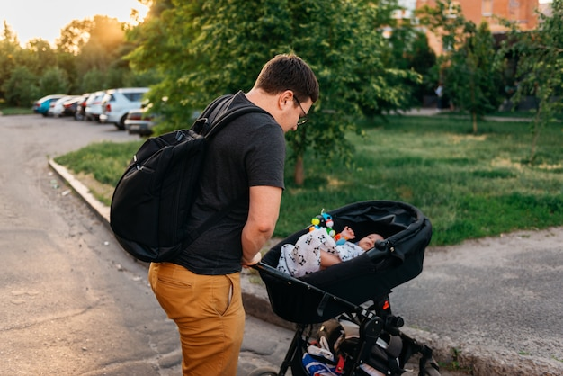 Father dad with newborn pram stroller outside during summer evening sunset