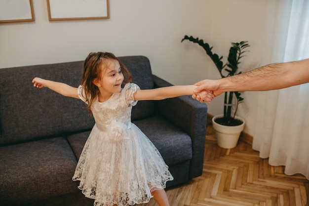 Father dancing with his small dressed in white daughter while having joy in the living room
