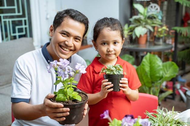 Father and daughter are holding potted plants and smiling at the camera
