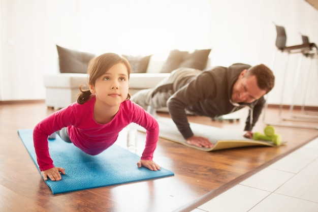 Father and daughter are training at home. sports at home.