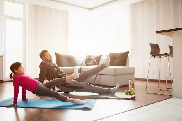 Father and daughter are training at home. workout in the apartment. sports at home. rreverce plank with leg raise on the floor at home