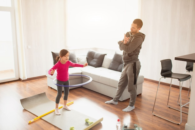 Father and daughter are training at home. workout in the apartment. sports at home. she tweaks a hula hoop and dad uses a sports watch to measure time
