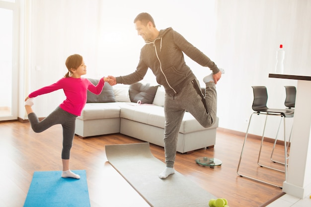Father and daughter are training at home. workout in the apartment. sports at home. they do exercises with yoga or pilates.