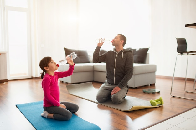 Father and daughter are training at home. workout in the apartment. sports at home. they sit on yoga mats and drink water. you need clean water to drink your sport time.