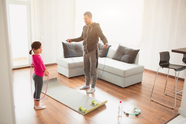 Father and daughter are training at home. workout in the apartment. sports at home. they use a rubber rope for training