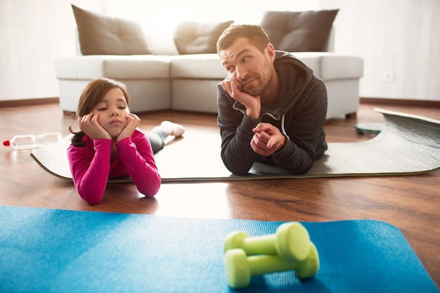 Father and daughter are training at home. workout in the apartment. sports at home.