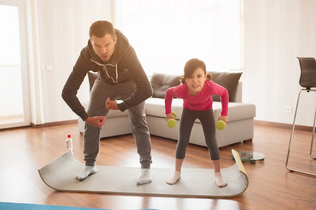 Father and daughter are training at home. workout in the apartment.