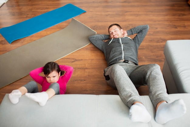 Father and daughter are training at home