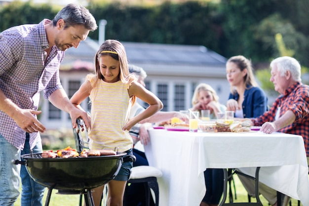 Father and daughter at barbecue grill while family having lunch