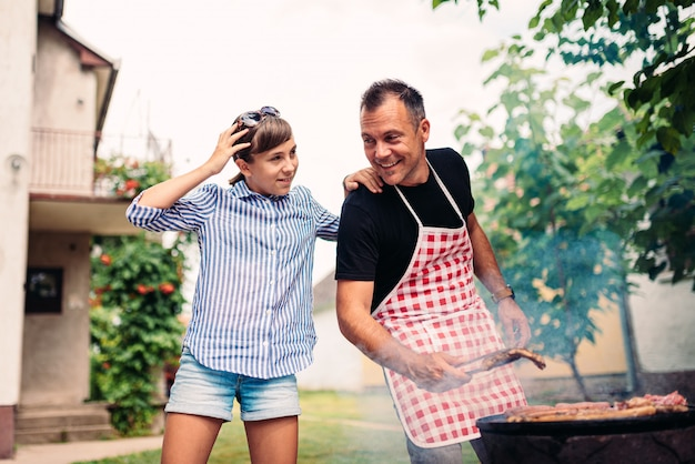 Father and daughter barbecuing meat