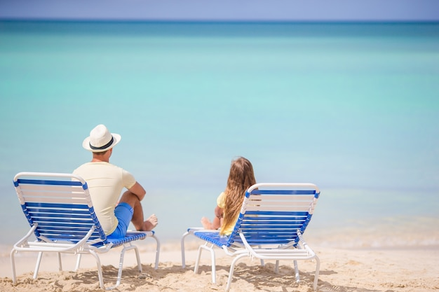 Father and daughter on beach sitting on chaise-longue