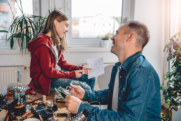 Father and daughter building robot and having fun