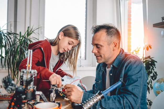 Father and daughter building robot