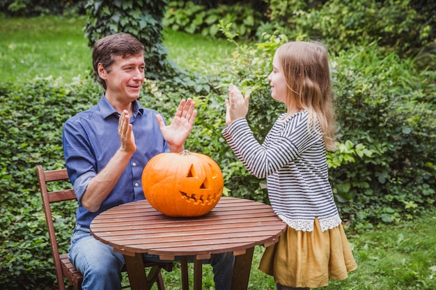 Father and daughter carving pumpkin for halloween