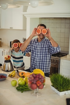 Father and daughter covering their eyes with blood orange