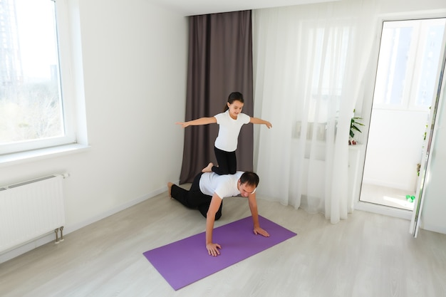 Father and daughter doing yoga at home