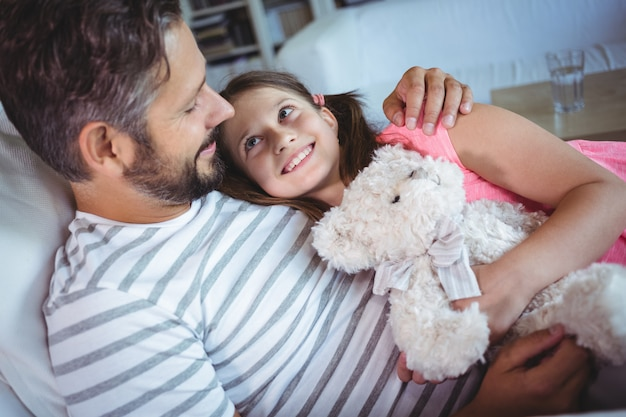 Father and daughter embracing on sofa