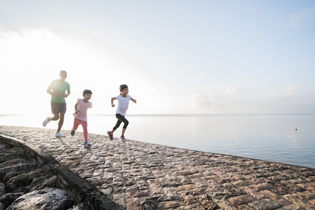 Father and daughter do exercises running outdoor racing each other