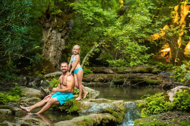A father and daughter family on a mountain river in the jungle.turkey.
