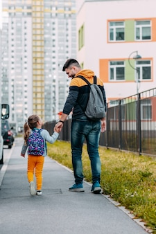 Father and daughter going to school for the first time. back to school after pandemic.