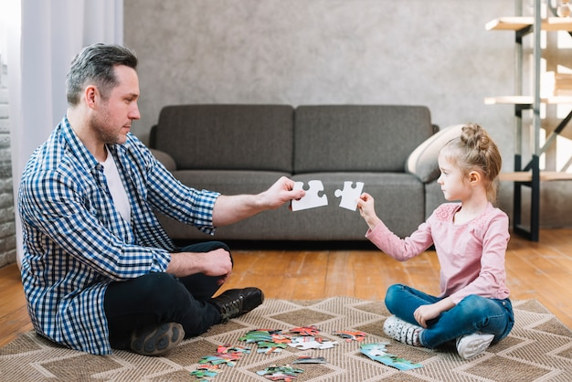 Father and daughter hand holding jigsaw puzzle piece