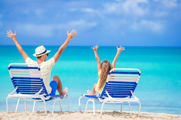 Father and daughter hands up on beach sitting on chaise-longue