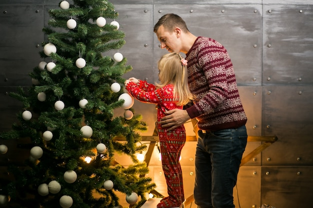 Father and daughter hanging toys on a christmas tree