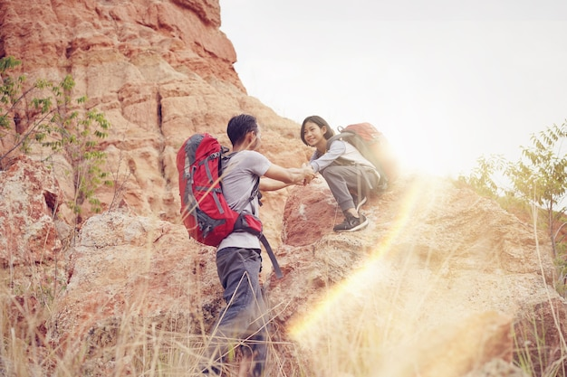 Father and daughter hiking climbing in mountains together success idea concept