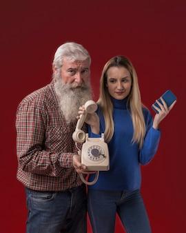 Padre e figlia che tengono vecchio telefono