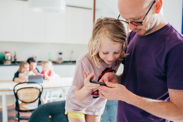 Father and daughter indoor using phone