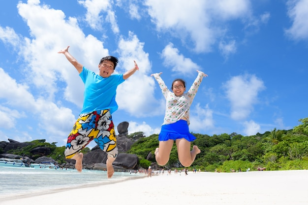 Father and daughter jumping with happy on beach near the sea under blue sky and cloud of summer at koh similan island in mu ko similan national park, phang nga province, thailand