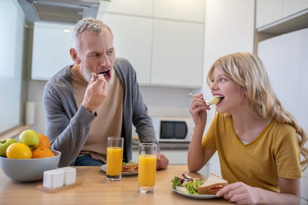 A father and a daughter in the kitchen having breakfast