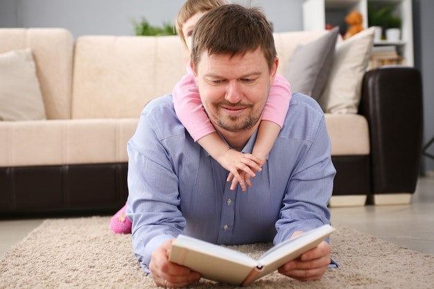 Father and daughter lie on floor reading interesting book