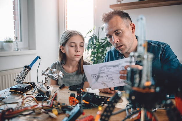 Father and daughter looking at electronic schematics
