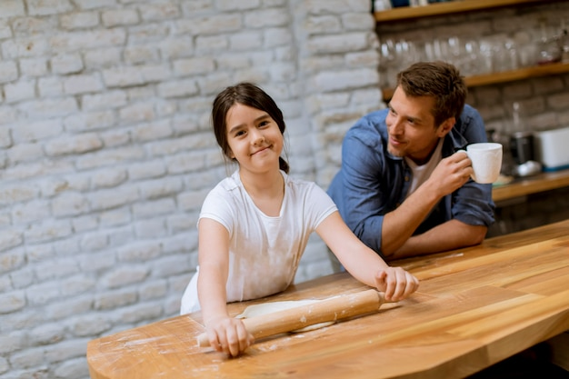 Father and daughter making bread in the kitchen