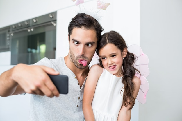 Father and daughter making faces while taking self portrait