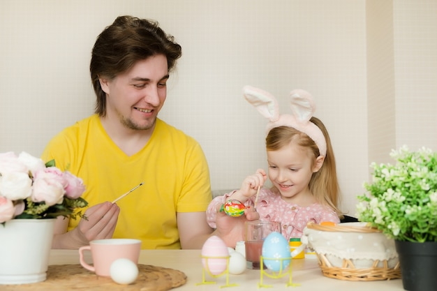 Father and daughter painting eggs for easter