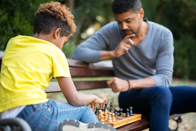 Father and daughter playing chess on the bench in city park