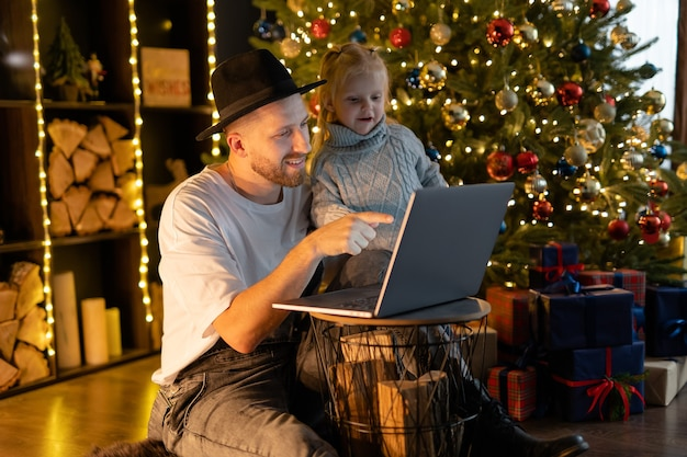 Father and daughter playing game on laptop computer. happy family time - modern lifestyle. christmas