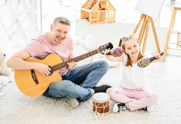 Father and daughter playing musical instruments