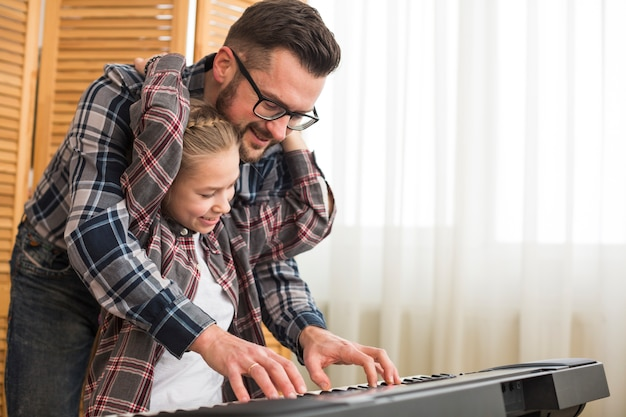 Father and daughter playing on the piano