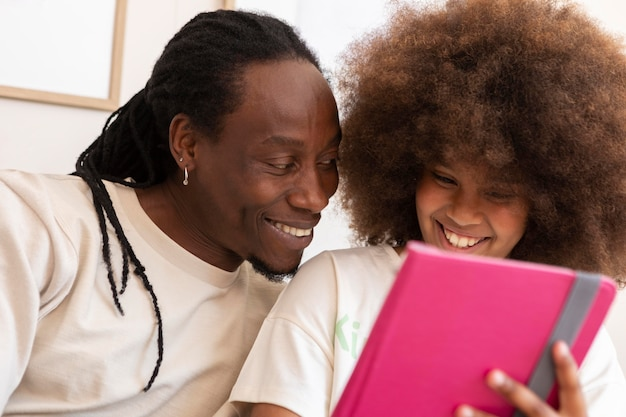 Father and daughter playing together on a tablet