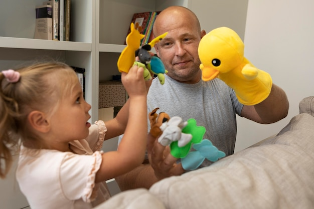 Father and daughter playing with cute puppets