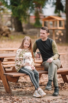 Father and daughter playing with dog outdoors