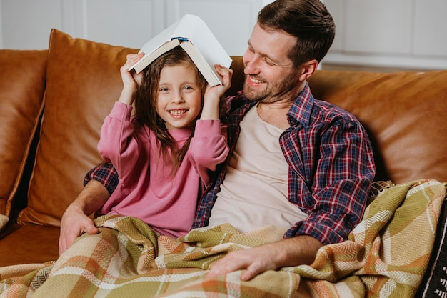 Father and daughter reading book at home together