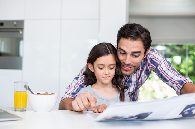 Father and daughter reading newspaper at home