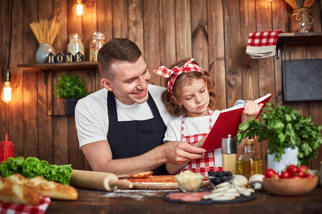 Father and daughter reading recipes book while cooking pizza