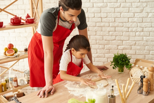 Father and daughter roll out the dough. dough rolling pin.