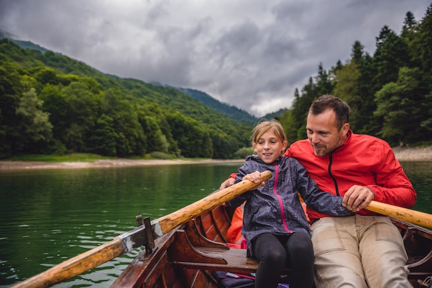 Father and daughter rowing a boat on the lake