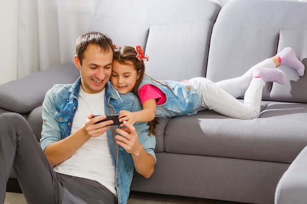 Father and daughter sharing something funny in a mobile phone